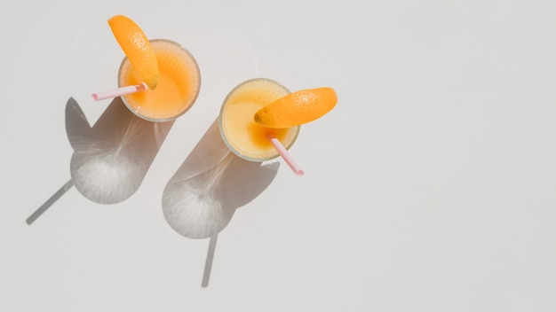 Glasses of natural juice of oranges with shadows top view