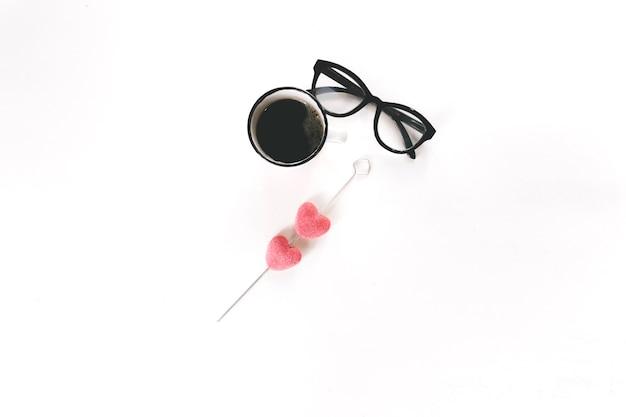 Glasses near coffee and sugar hearts