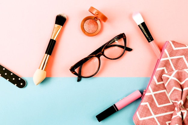 Glasses near makeup bagf and cosmetics