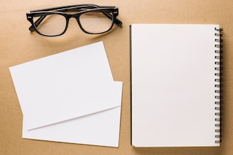 Glasses near notebook and paper sheets