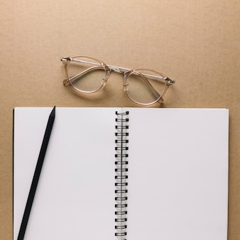 Glasses near notebook and pencil