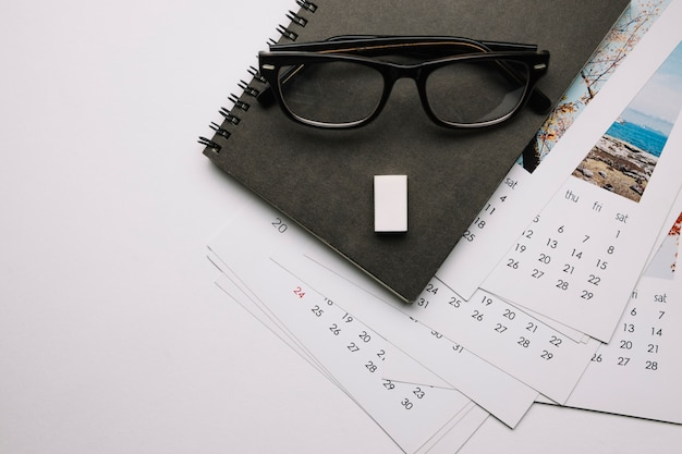 Glasses on notebook and calendars
