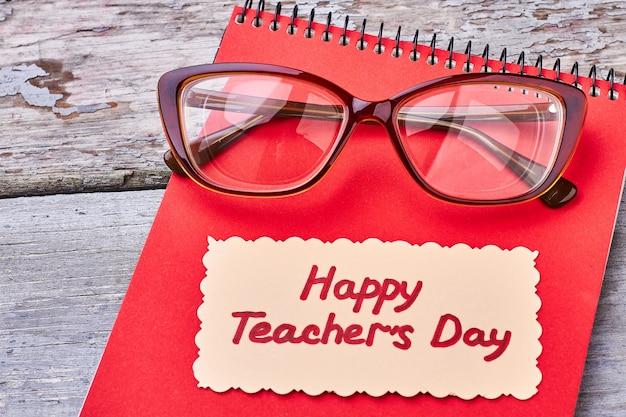 メガネ、木の表面にノートブック。親愛なる先生への心からのご挨拶。