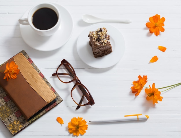 Glasses, notebook, pen and cup of coffee on white wooden table