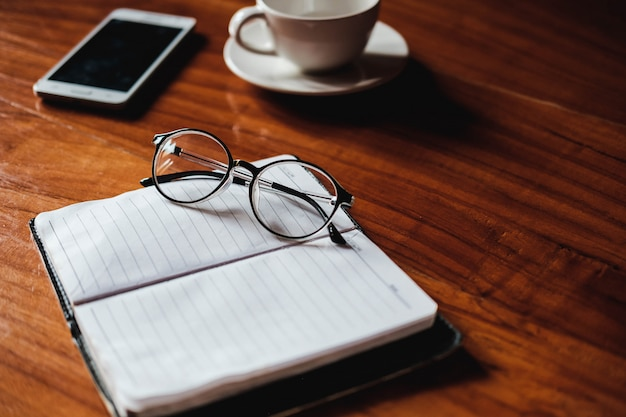 Glasses on notebooks, coffee cups on desks