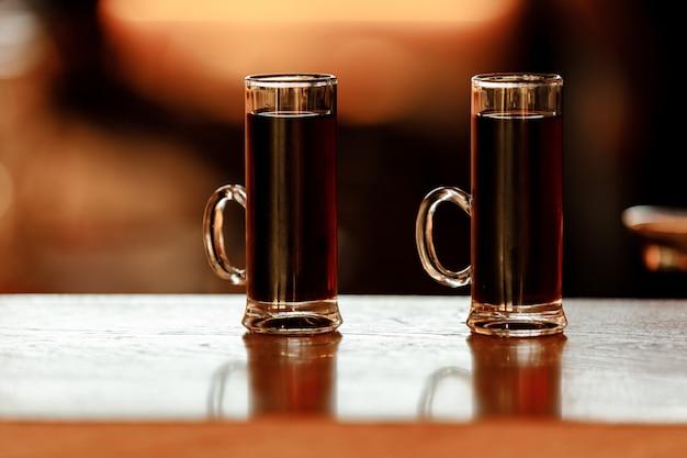 Стаканы алкогольных выстрелов на панели. мини-шутеры над деревянными