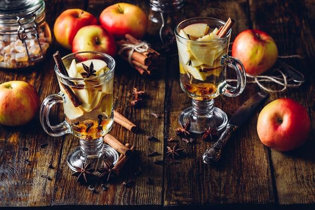 Стаканы яблочного пряного напитка с гвоздикой, корицей, анисовой звездочкой и темным леденцовым сахаром. все ингредиенты и некоторые кухонные принадлежности на деревянном столе. вертикальный.