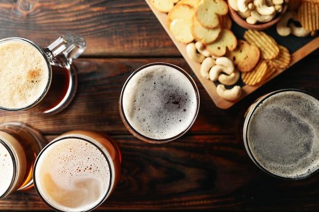 Бокалы пива и закуски на деревянном столе