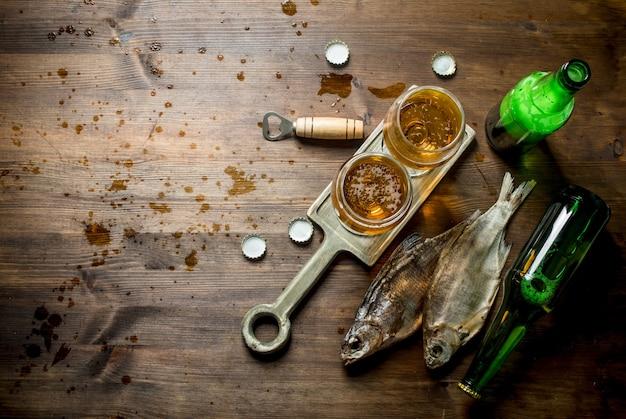 スタンドにビールと干物のグラス。木製の背景に