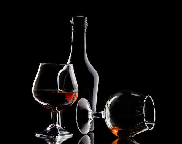 Бокалы бренди и бутылка на черном столе