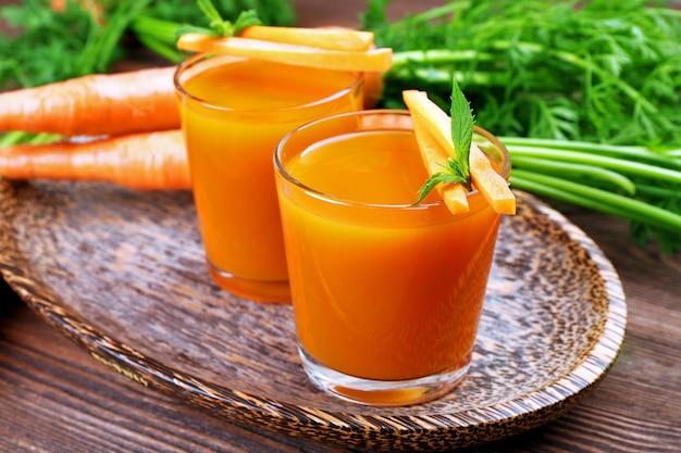 テーブルの上に野菜とにんじんジュースのグラスをクローズアップ