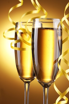 黄色い表面にシャンパンとストリーマーのグラス