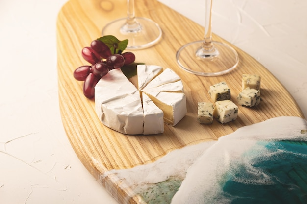 바다 파도 형태의 에폭시 수지로 장식 된 아름다운 전용 보드에 샴페인, 치즈, 와인 잔.