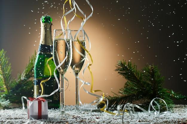 Бокалы шампанского, еловые ветки и подарок, праздничная тема. концепция партии