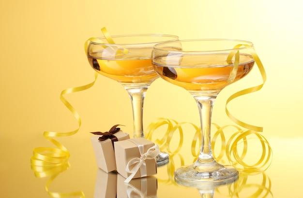 黄色の壁にシャンパン、ギフト、ストリーマーのグラス