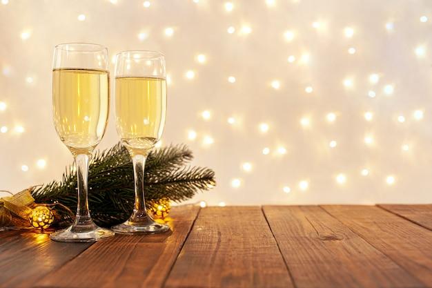 ぼやけた金色の花輪、大晦日のコンセプトと木製のテーブルにシャンパンのグラス