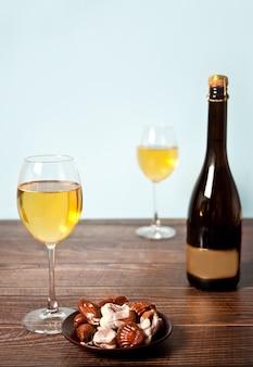 木製のテーブルの背景にチョコレートとボトルのプレートとシャンパンまたは白ブドウのワインのグラス。