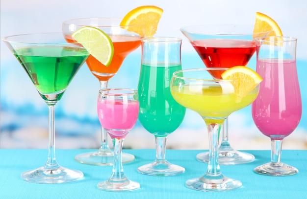 Бокалы коктейлей на столе у бассейна