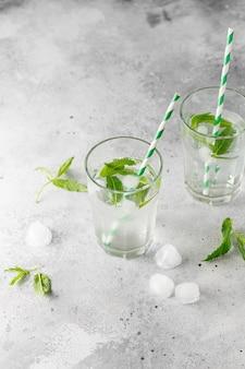회색 콘크리트에 신선한 민트 잎과 얼음 조각이있는 냉수 잔