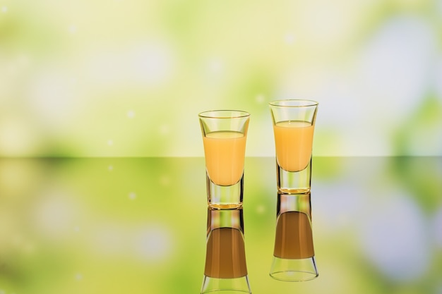 反射と緑の背景にクリームリキュールのグラス。レモンリキュールが不足しています。伝統的なイタリアのアルコール飲料リモンチェッロ