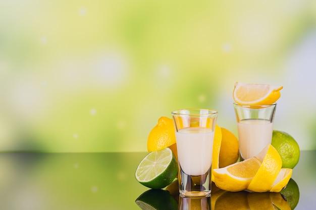 反射のある緑の背景にライムとレモンのクリームリキュールのグラス。レモンリキュールが不足しています。伝統的なイタリアのアルコール飲料リモンチェッロ