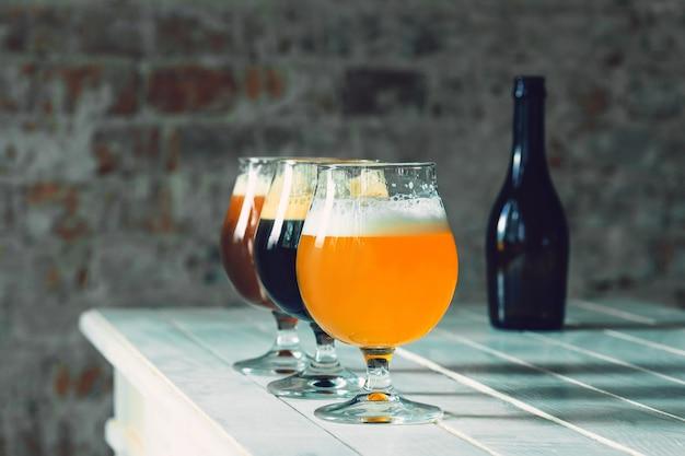 並んでいる木製のテーブルにさまざまな種類のダークビールとライトビールのグラス。大きな友達のパーティーのために、冷たいおいしい飲み物が用意されています。飲み物、楽しみ、会議、オクトーバーフェストの概念。