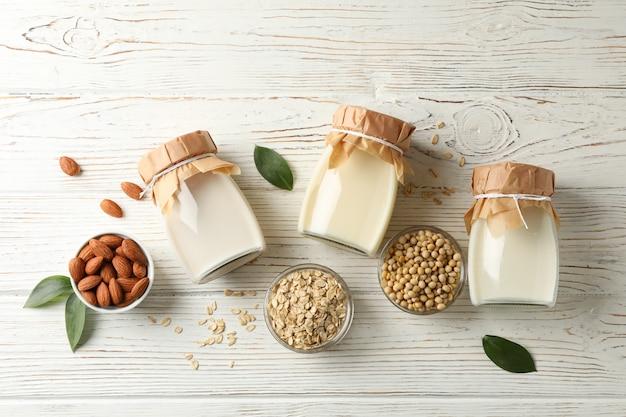 Стекла разных видов молока на белой древесине, взгляд сверху. пространство для текста