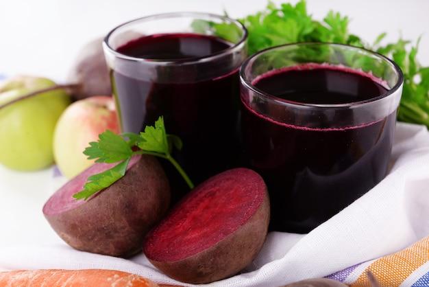 Стаканы свежего свекольного сока и овощей на разделочной доске крупным планом