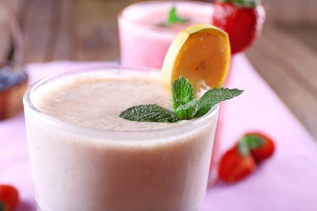 新鮮な冷たいスムージーとフルーツとベリーのグラス、テーブルの上、クローズアップ
