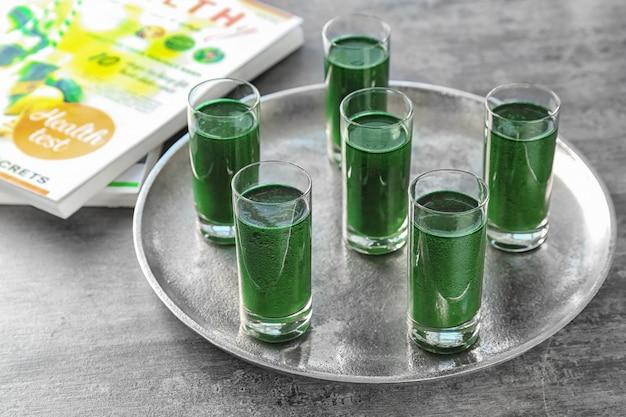 금속 쟁반에 신선한 녹색 스무디 잔