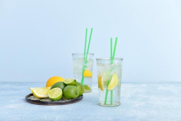 テーブルの上に柑橘系の果物と新鮮な注入水のグラス