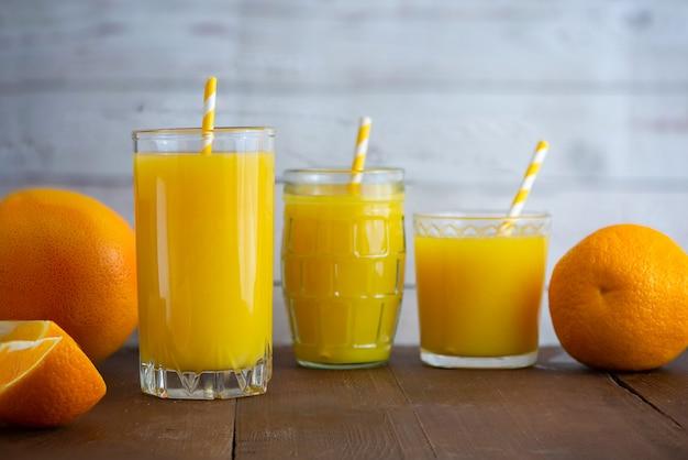軽い木製の背景に新鮮なオレンジジュースのグラス。側面図