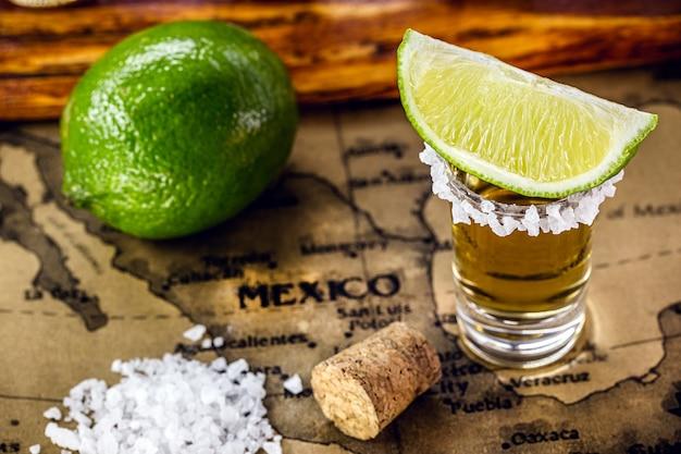 ブラジルのヴィンテージ地図の上に、塩とレモンを添えた黄金のテキーラのグラス