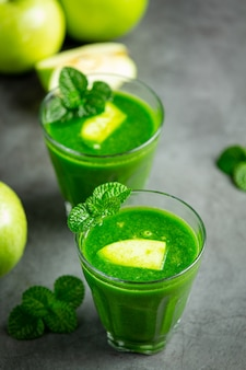新鮮な青リンゴの隣に置かれた青リンゴの健康的なスムージーのグラス