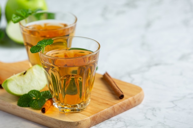 新鮮な青リンゴの隣に置かれた青リンゴの健康的なお茶のグラス