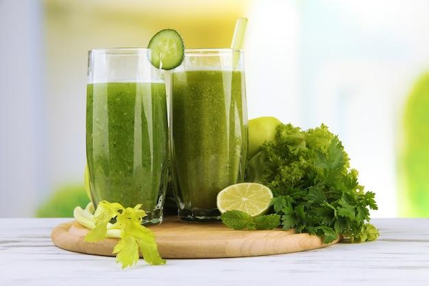Очки зеленого овощного сока на деревянном столе на ярком фоне