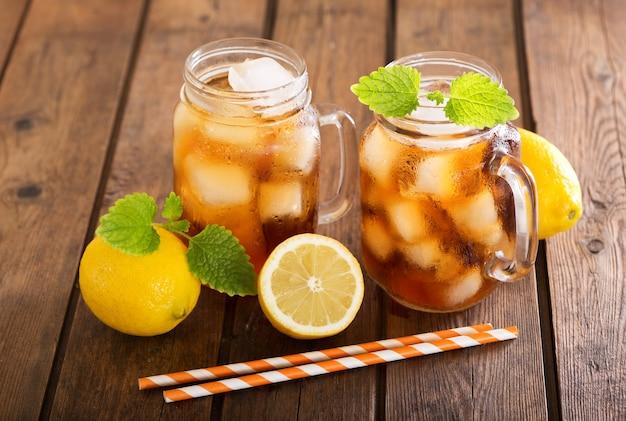 나무 테이블에 신선한 레몬과 아이스 티 잔
