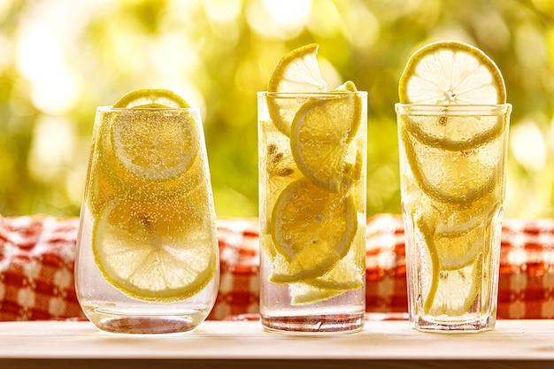 Стаканы лимонада с лимоном в солнечном саду