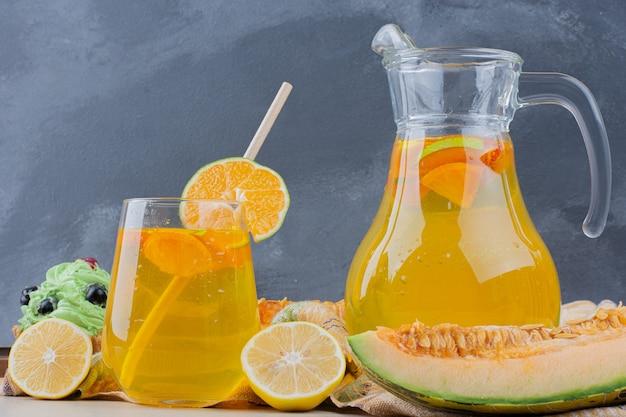 青い壁にレモンスライスとレモネードのグラス。