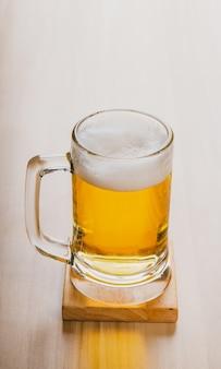 軽いビールのグラス、木製のテーブルの上のグラスに冷たいクラフトビール