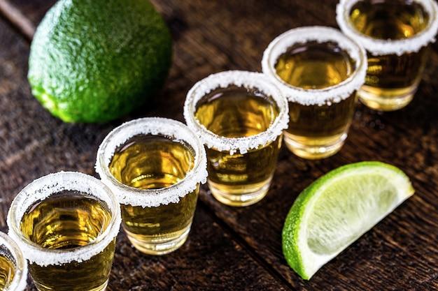 木の表面にレモンと塩が入ったメキシカンゴールドテキーラのグラス
