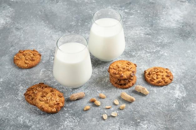 대리석 테이블에 유기농 땅콩을 곁들인 우유 한 잔과 홈메이드 쿠키.