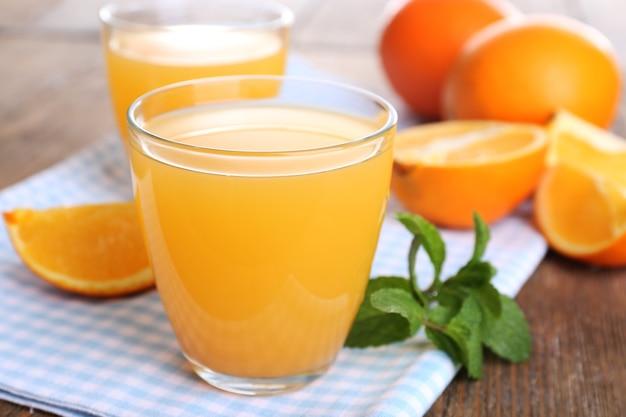 木製のテーブルにオレンジとオレンジジュースのグラスをクローズアップ