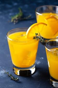 タイムの葉と青い背景の上のオレンジのスライスとオレンジジュースのグラス