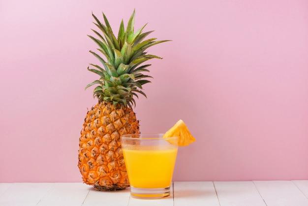 ピンクの背景の上のテーブルにパイナップルジュースのグラス