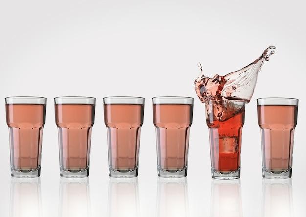 角氷と1つのグラスにスプラッシュとピンクのレモネードのグラス