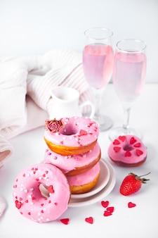베이킹 선반에 핑크 와인 또는 샴페인과 핑크 도넛의 안경. 발렌타인 데이 개념.