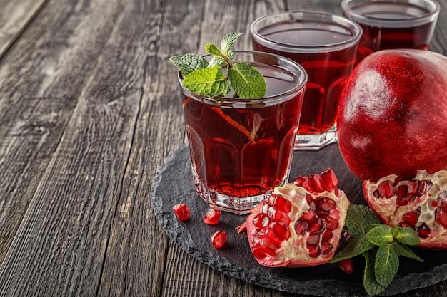 Стаканы гранатового сока со свежими плодами граната и мятой, концепция здорового напитка
