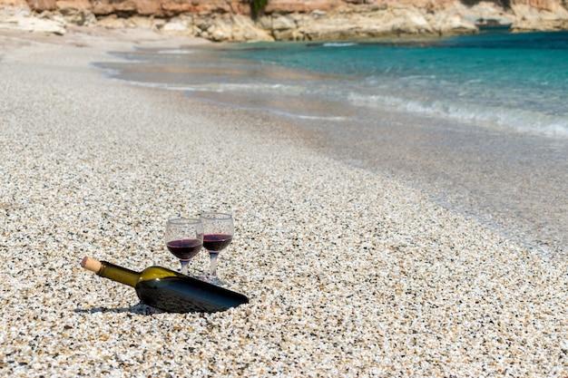 Бокалы красного вина и бутылка на пляже в солнечный летний день
