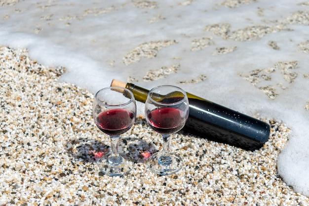 여름 화창한 날에 해변에서 레드 와인과 병의 안경